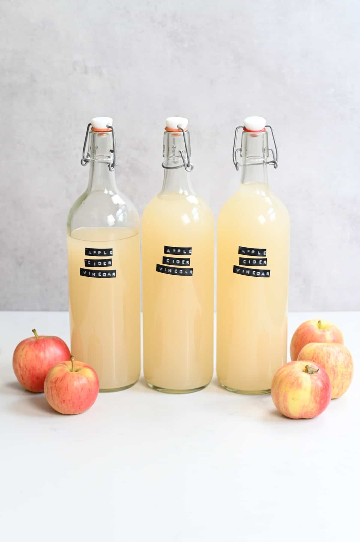 Three bottles of apple cider vinegar and a few apples next to them