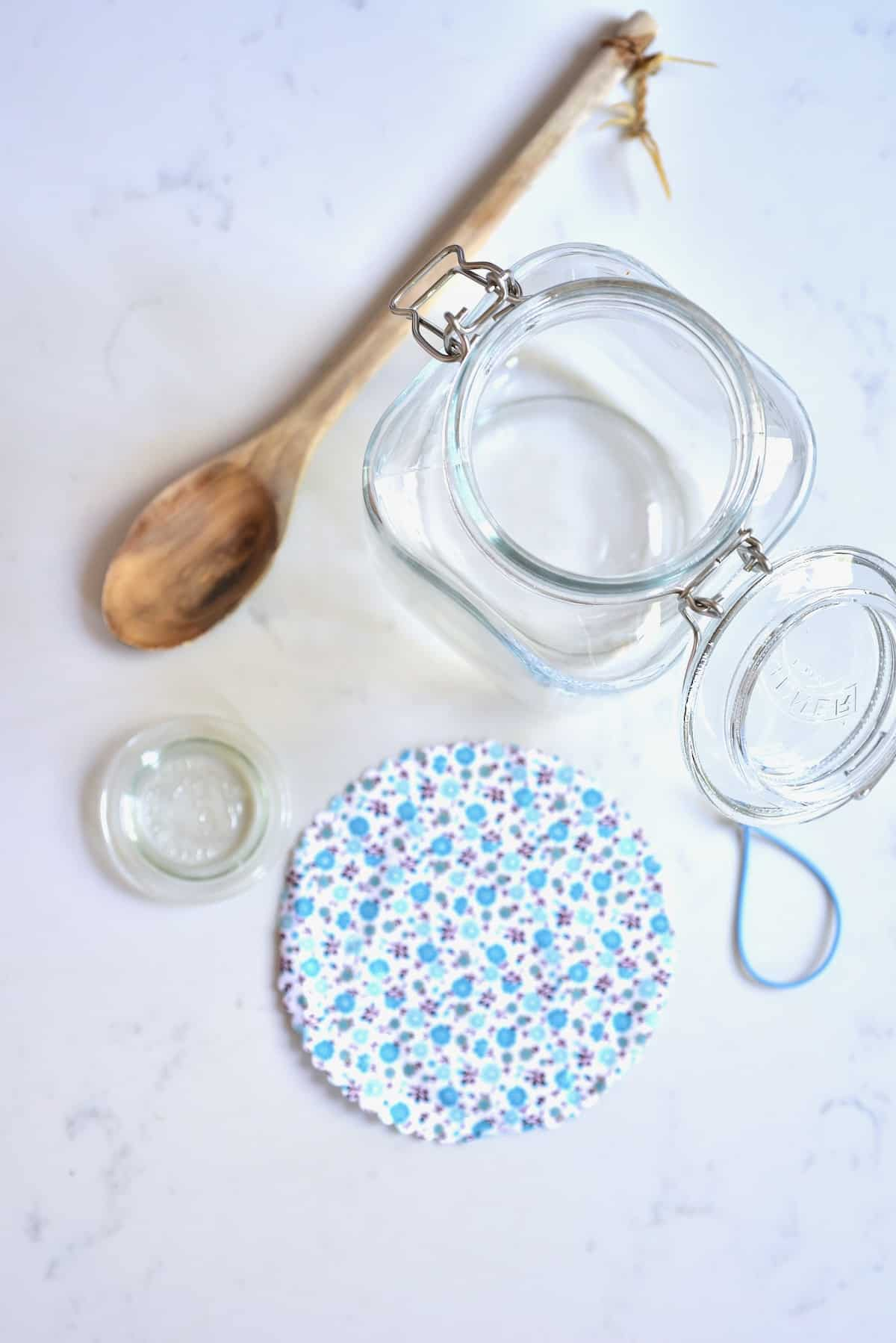 sterilised glass jar wooden spoon and a cloth cover