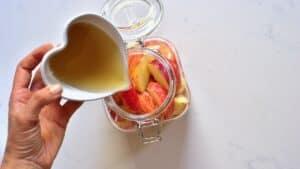 Adding sugar to apples in a jar