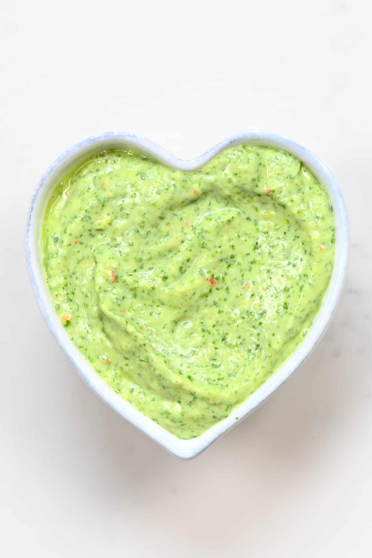 Creamy Avocado Cilantro Sauce in a heart shaped bowl