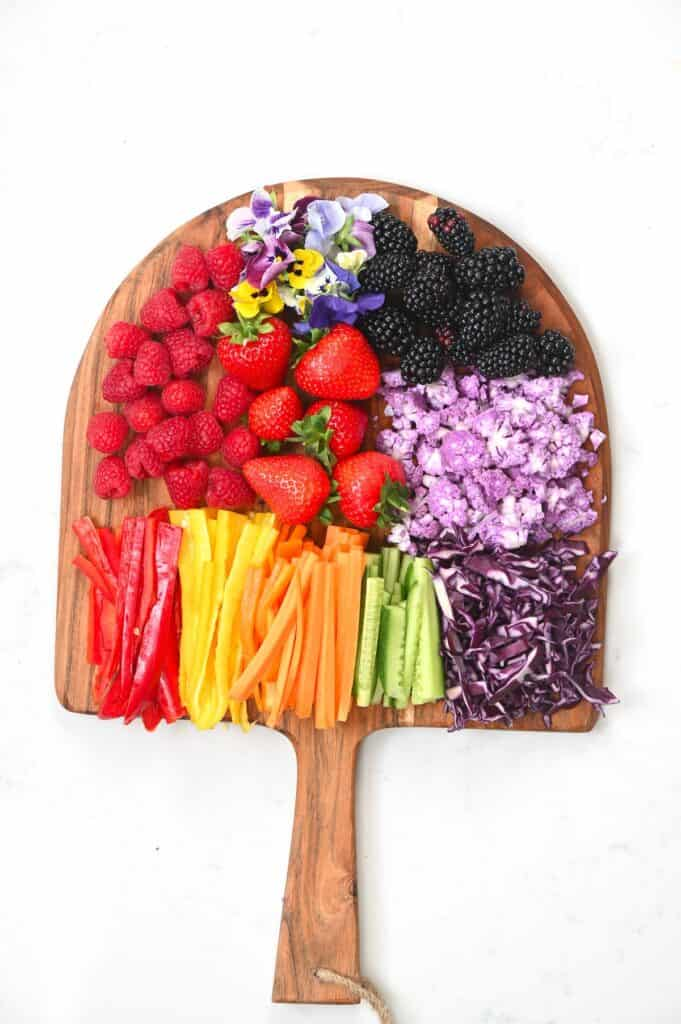 Chopped colorful vegetables and berries on a wooden board