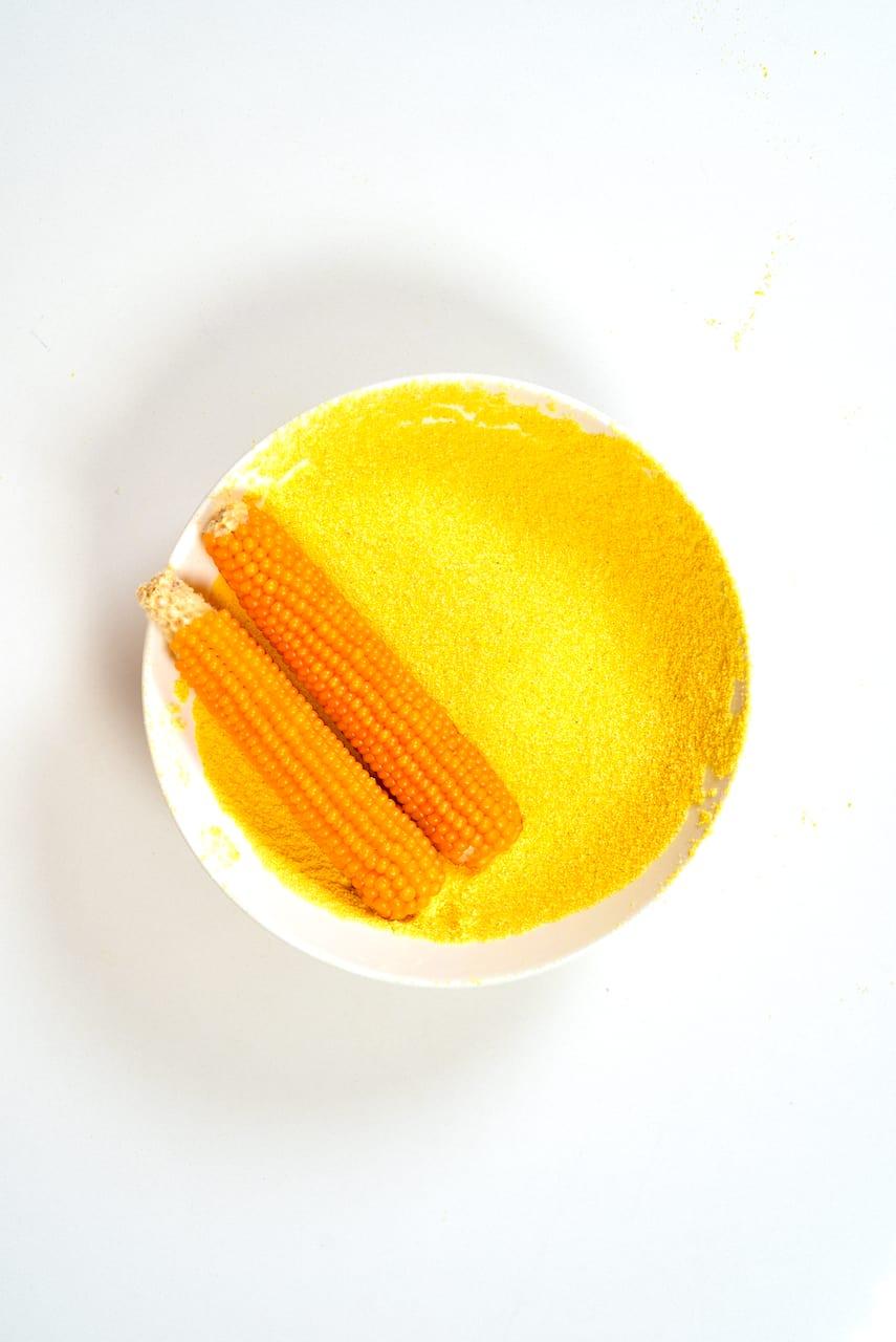 Corn flour in a bowl and corn ears