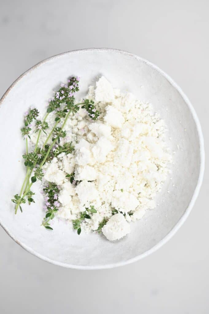 Crumbled goats cheese with herbs in a white plate