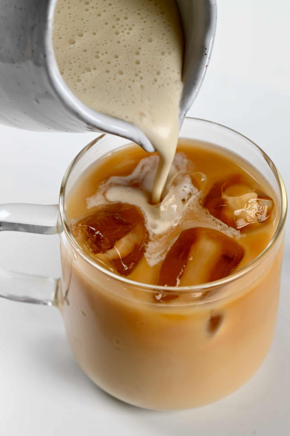 Pouring cream into an iced latte
