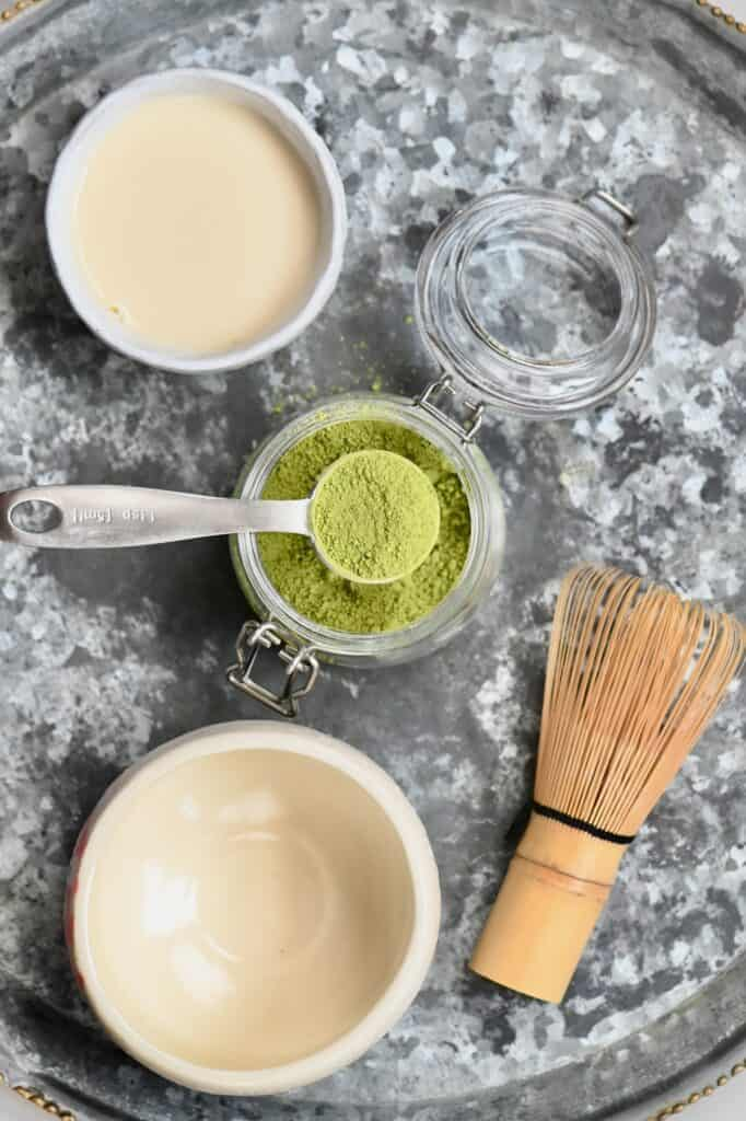 Small bowl of oat milk and teaspoon of matcha next to a bowl