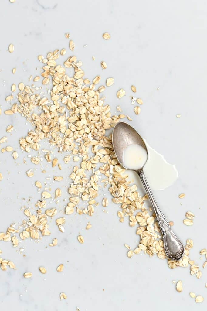 A spoon with oat creamer laying on a surface and oats next to it