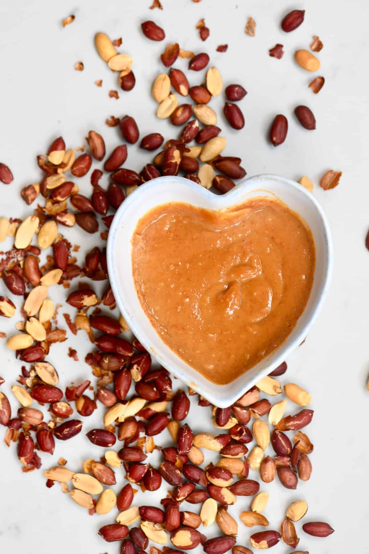 Peanut Dipping Sauce in a bowl surrounded with roasted peanuts