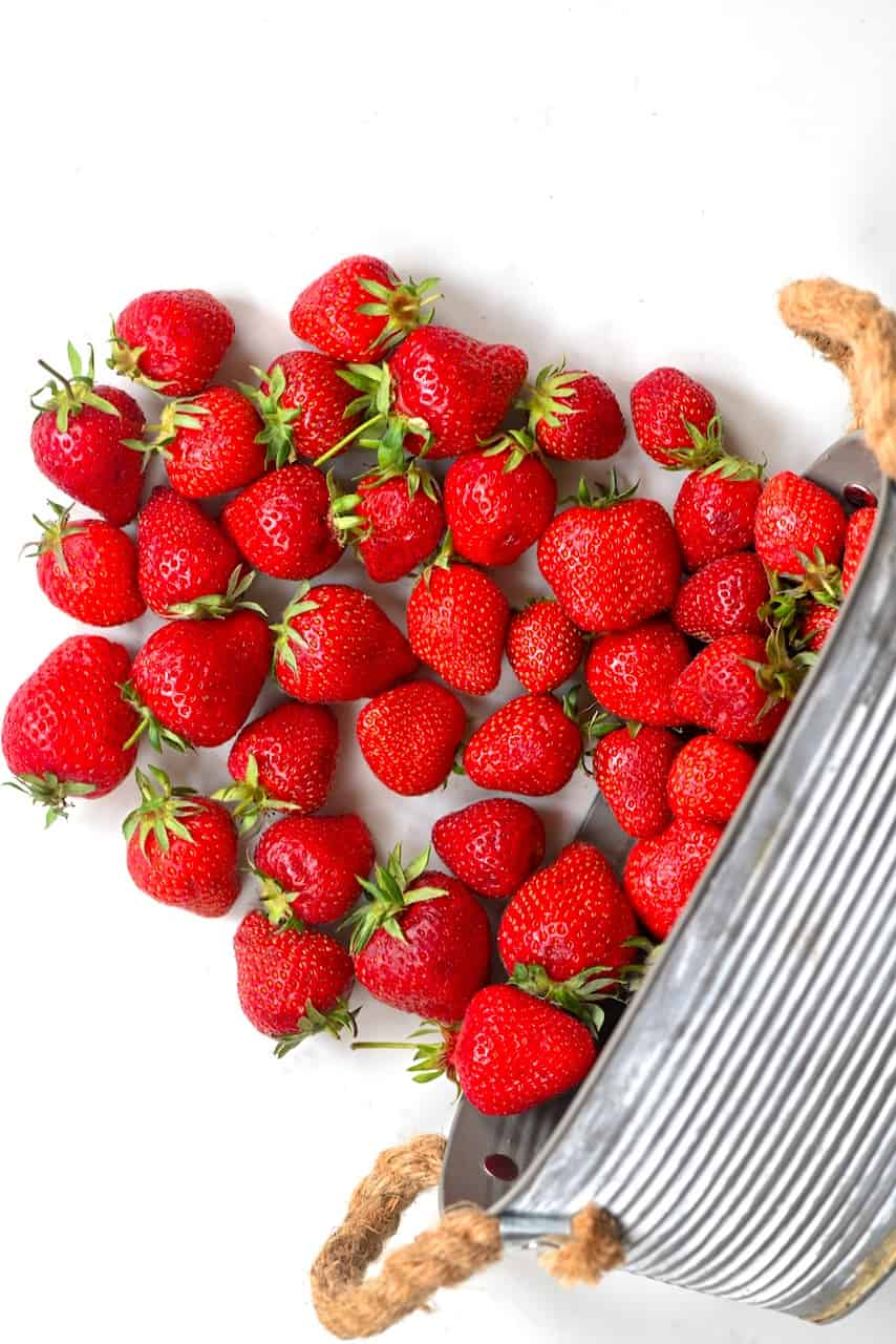 Strawberries coming from a basket on white marble
