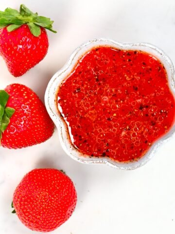 Strawberry Salad Dressing in a small bowl and three strawberries
