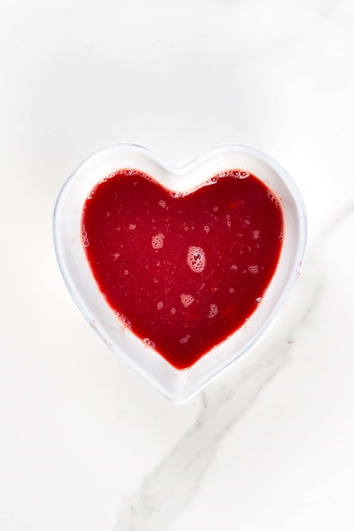 Strawberry syrup in a heart shaped bowl