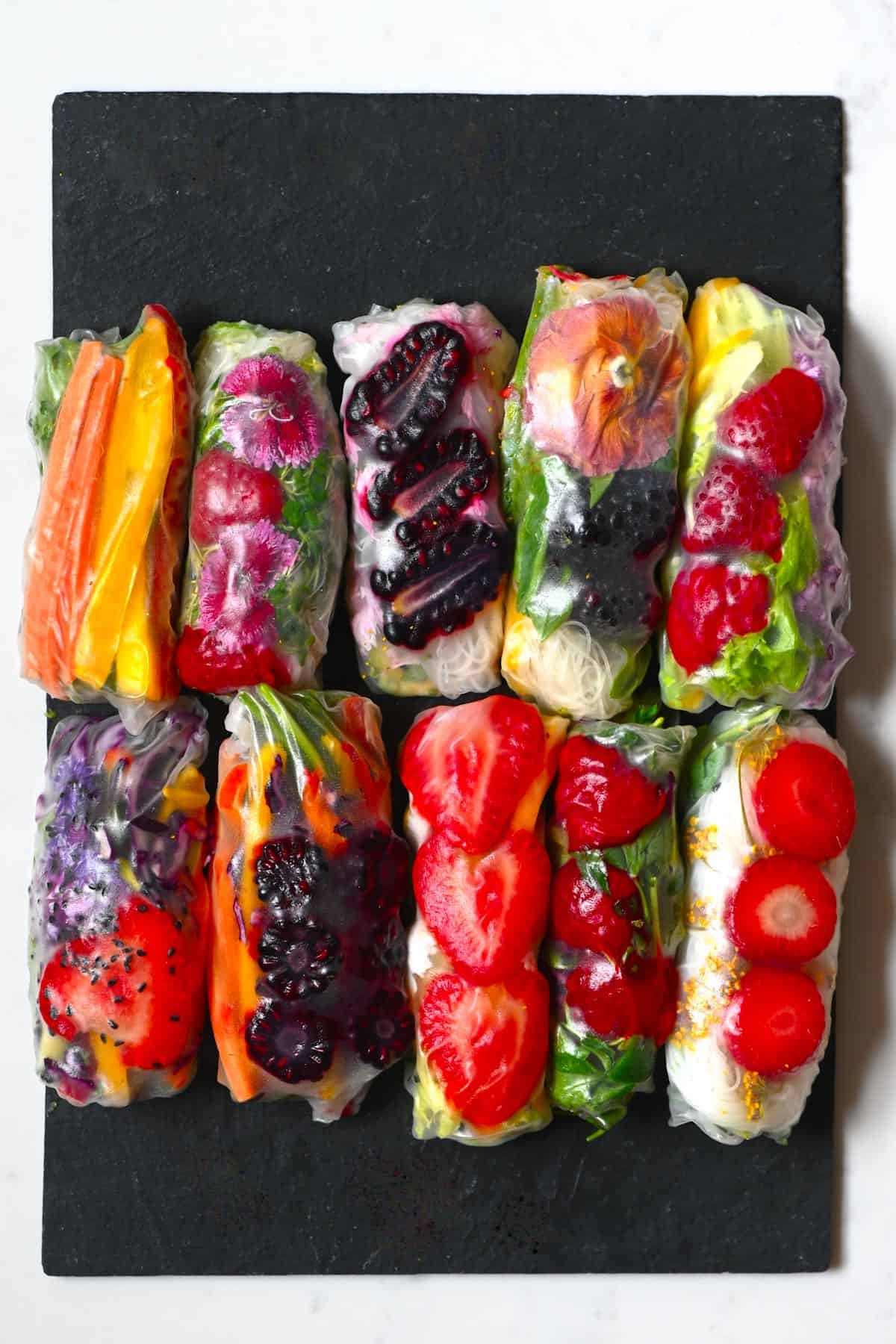 colorful fruit and vegetables rice paper rolls on a black slate