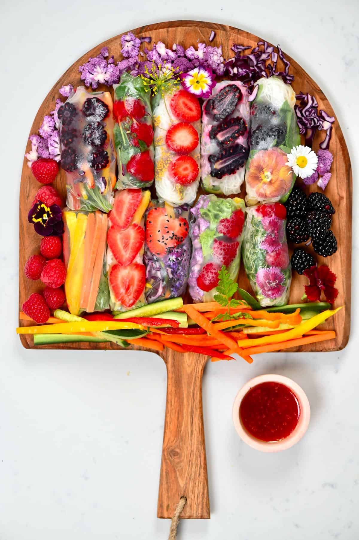 colorful fruit and vegetables rice paper rolls on a wooden board and a dipping sauce