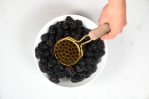 mashing Blackberries with a potato masher