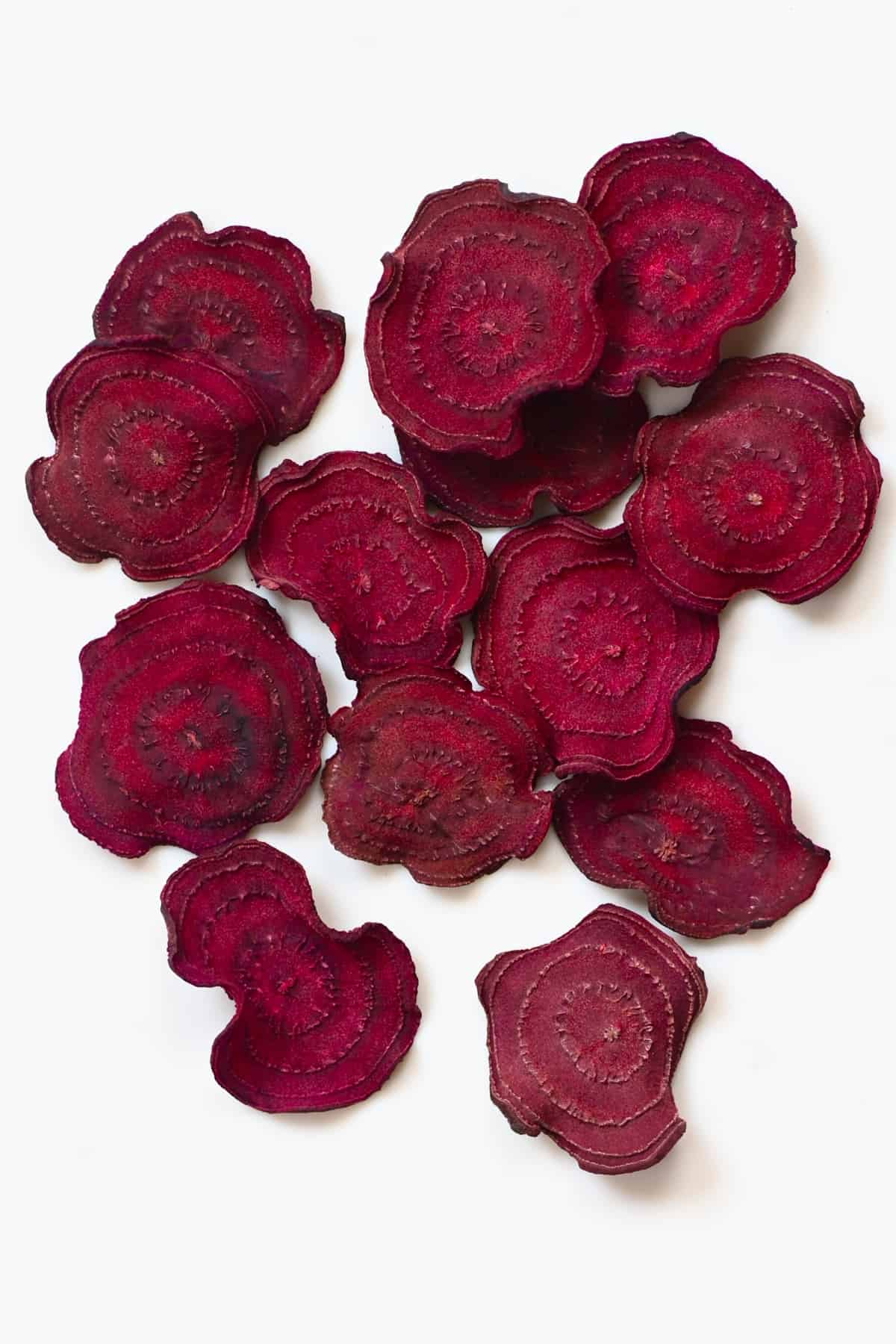 Homemade beetroot chips on a white surface