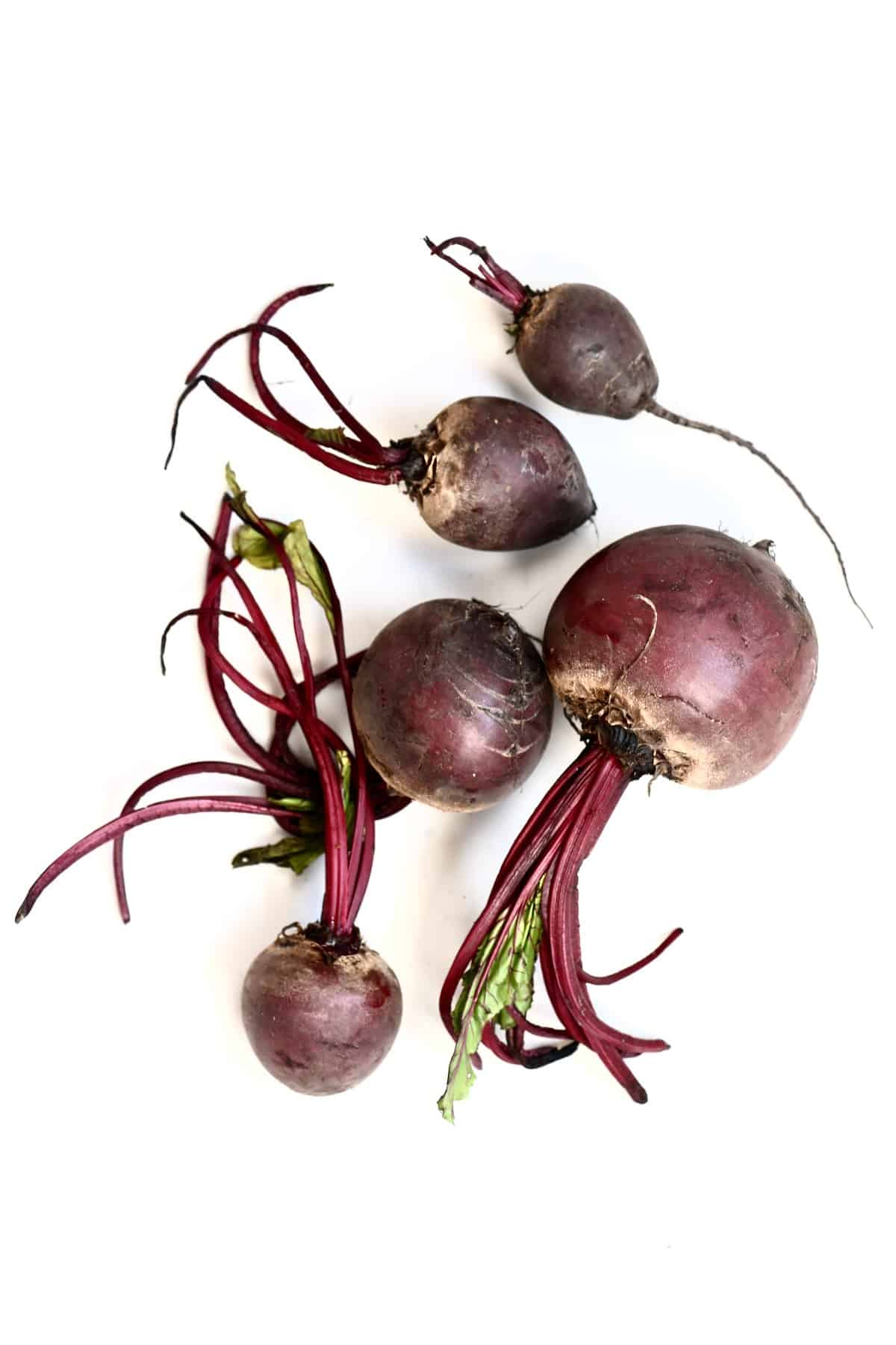 Five beetroots on a white surface