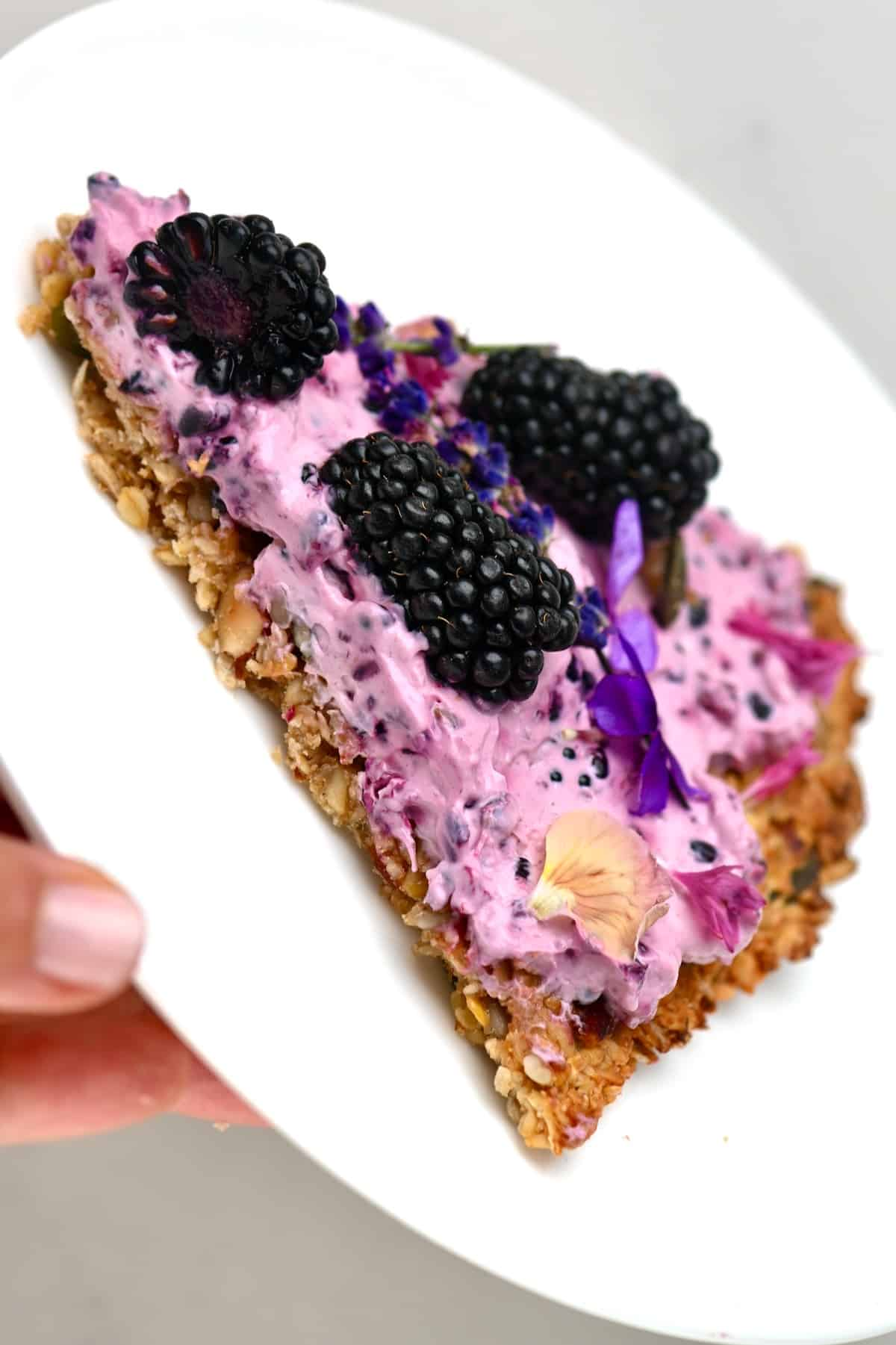 Close up of a slice of Blackberry granola pizza on a white plate