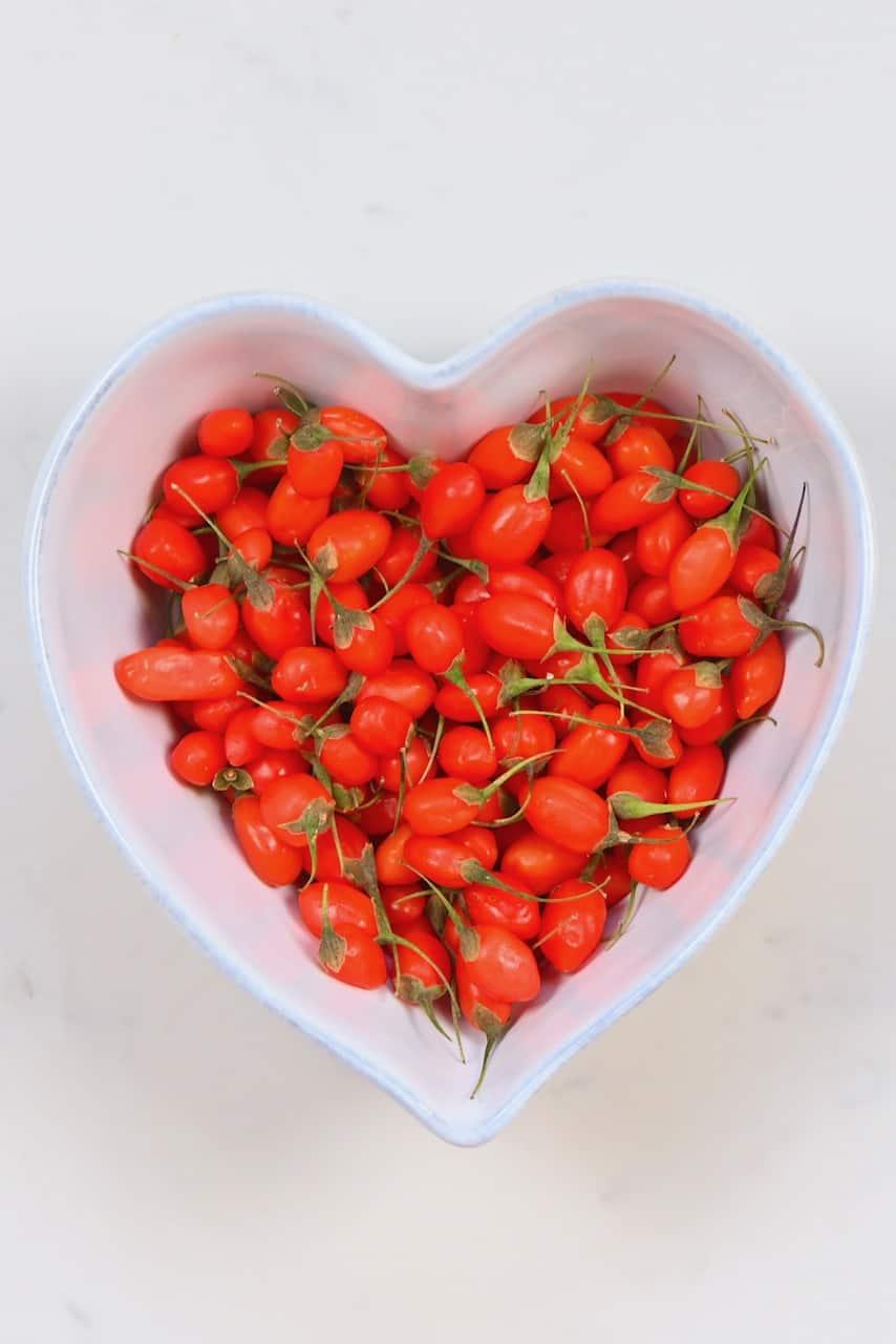 Fresh goji berries in a heart shaped bowl