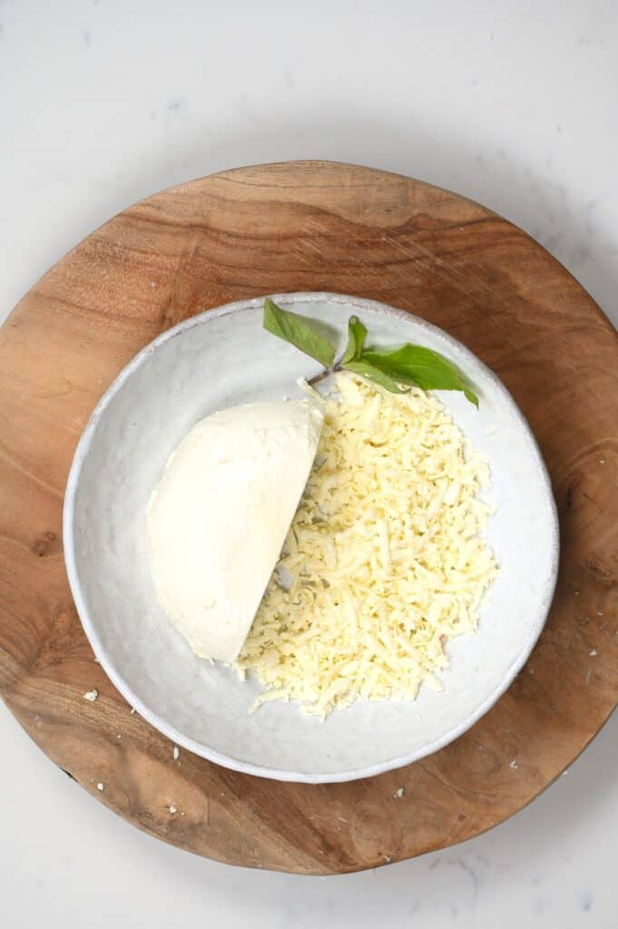 Half-grated mozzarella cheese in a bowl with a mint leaf