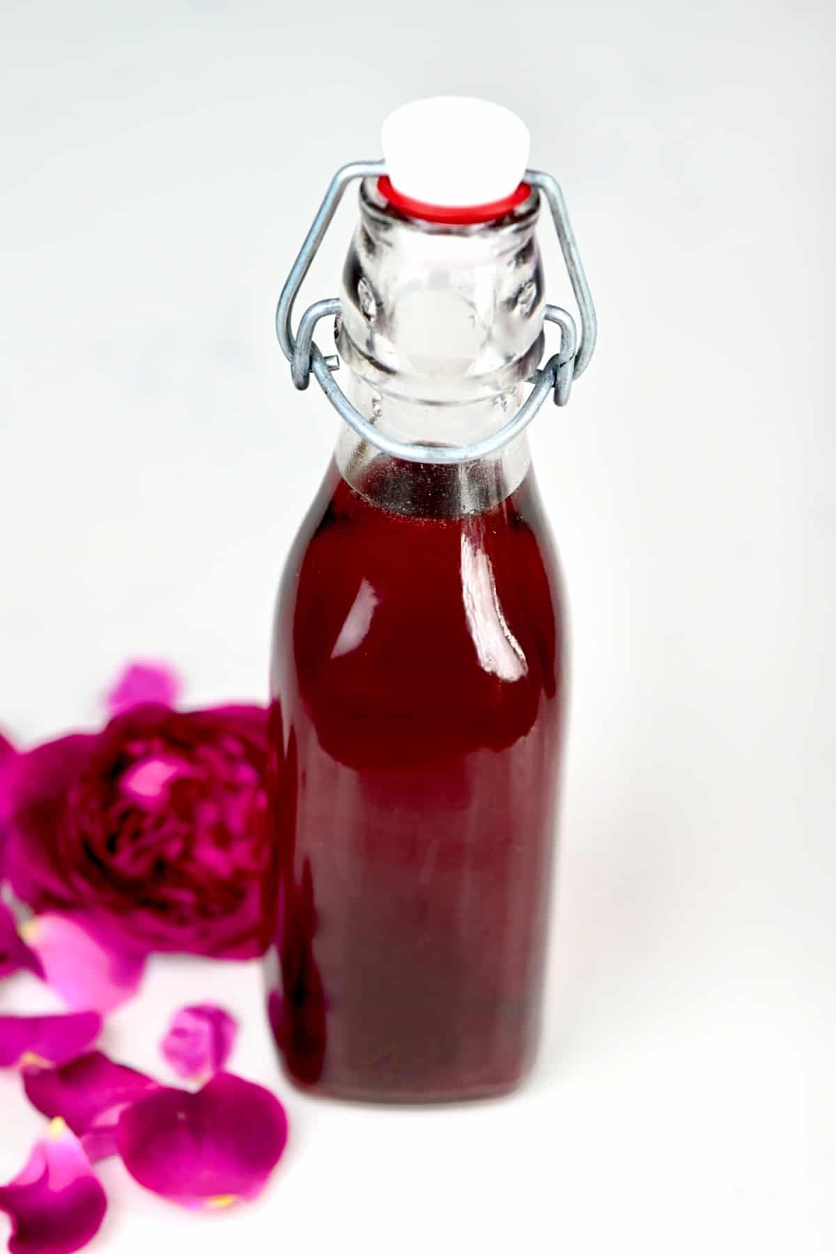 Rose Extract in a glass bottle with fresh roses in the side