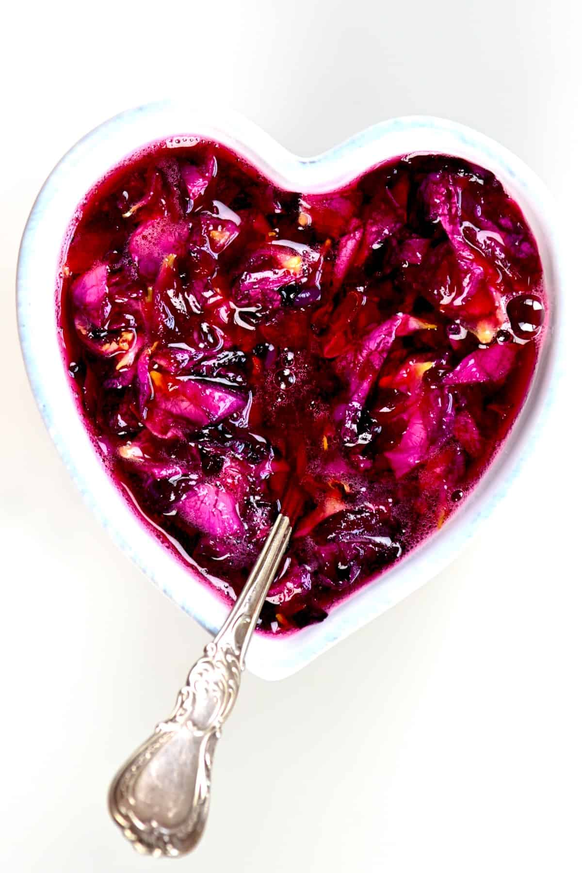Rose Jam in a heart shaped bowl with a spoon