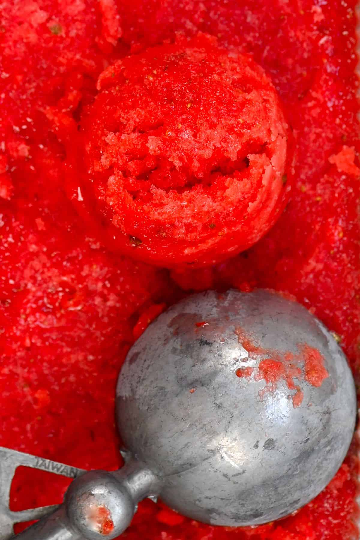 close up of a strawberry sorbet ball with an ice cream scoop