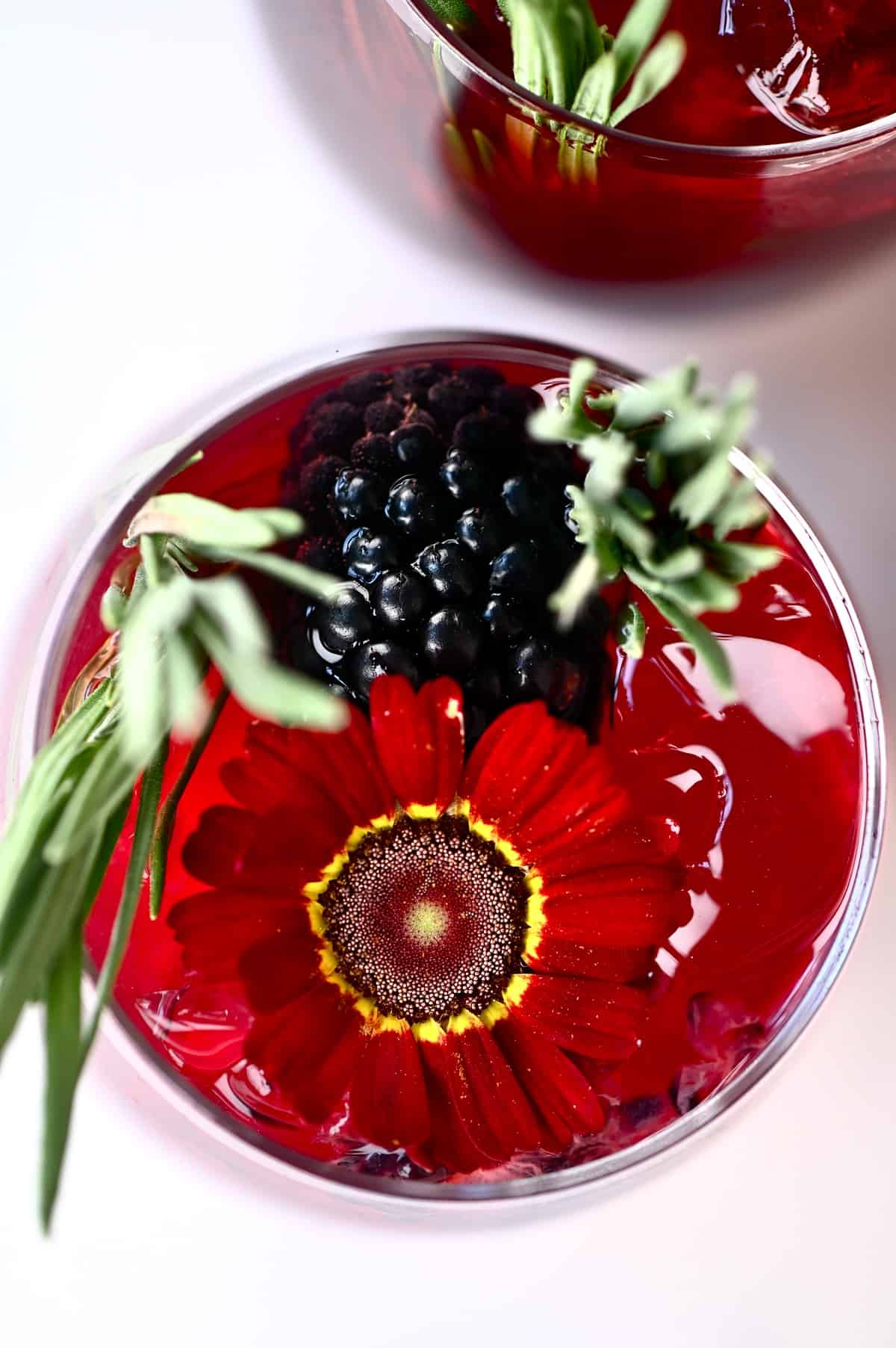 Top view of a blackberry iced tea in a glass decorated with edible flowers and herbs