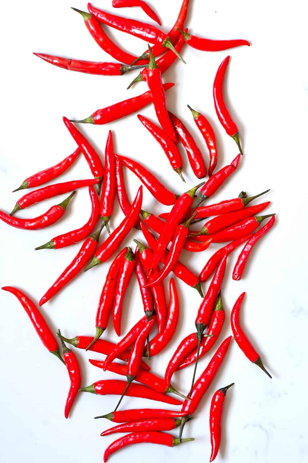 Red chili peppers on a white surface