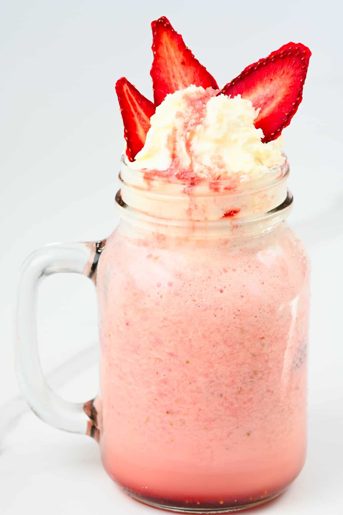 A mason jar with strawberry Frappuccino topped with cream and strawberries
