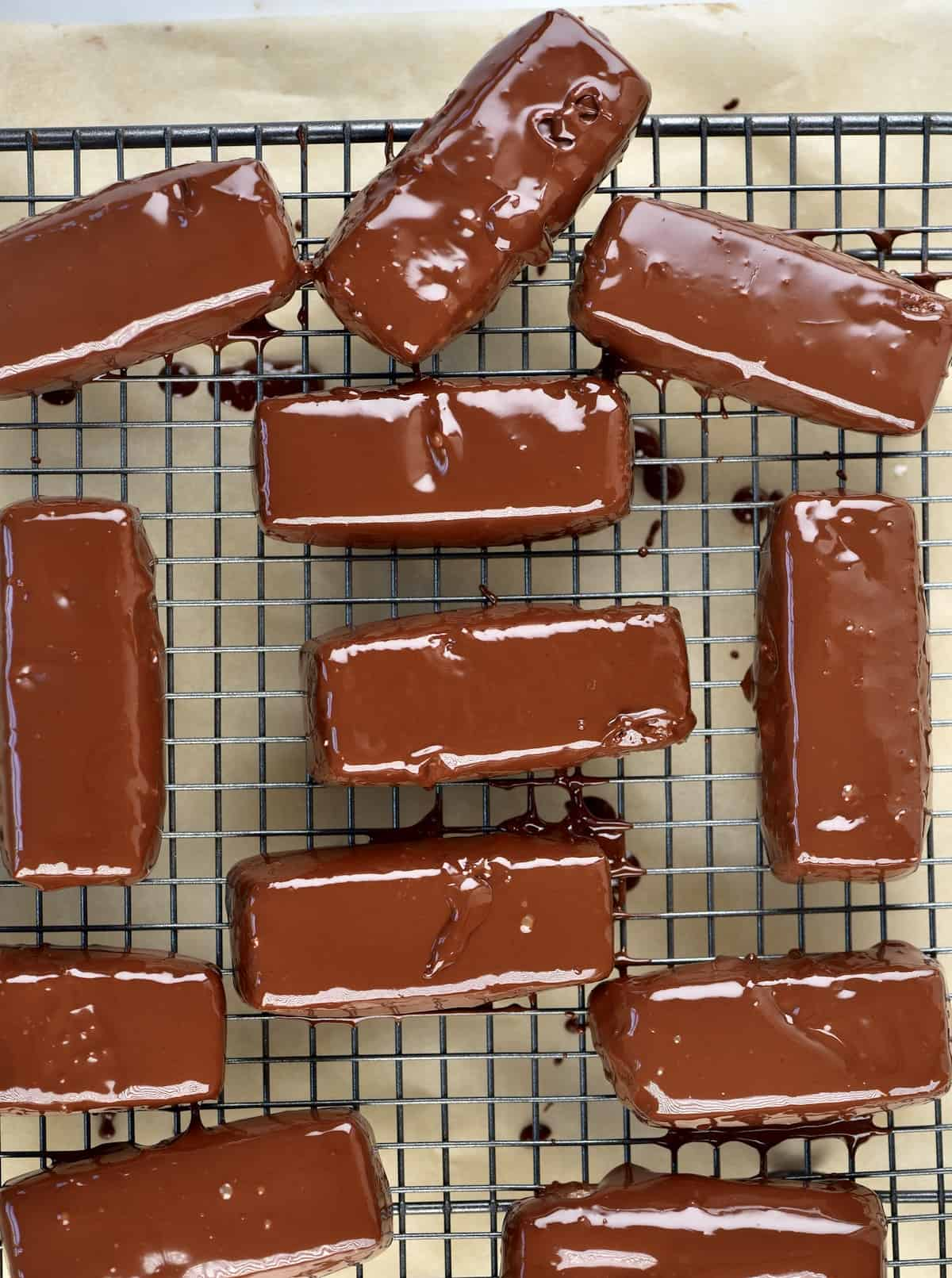 Bounty bars coated in chocolate drying on a cooling rack