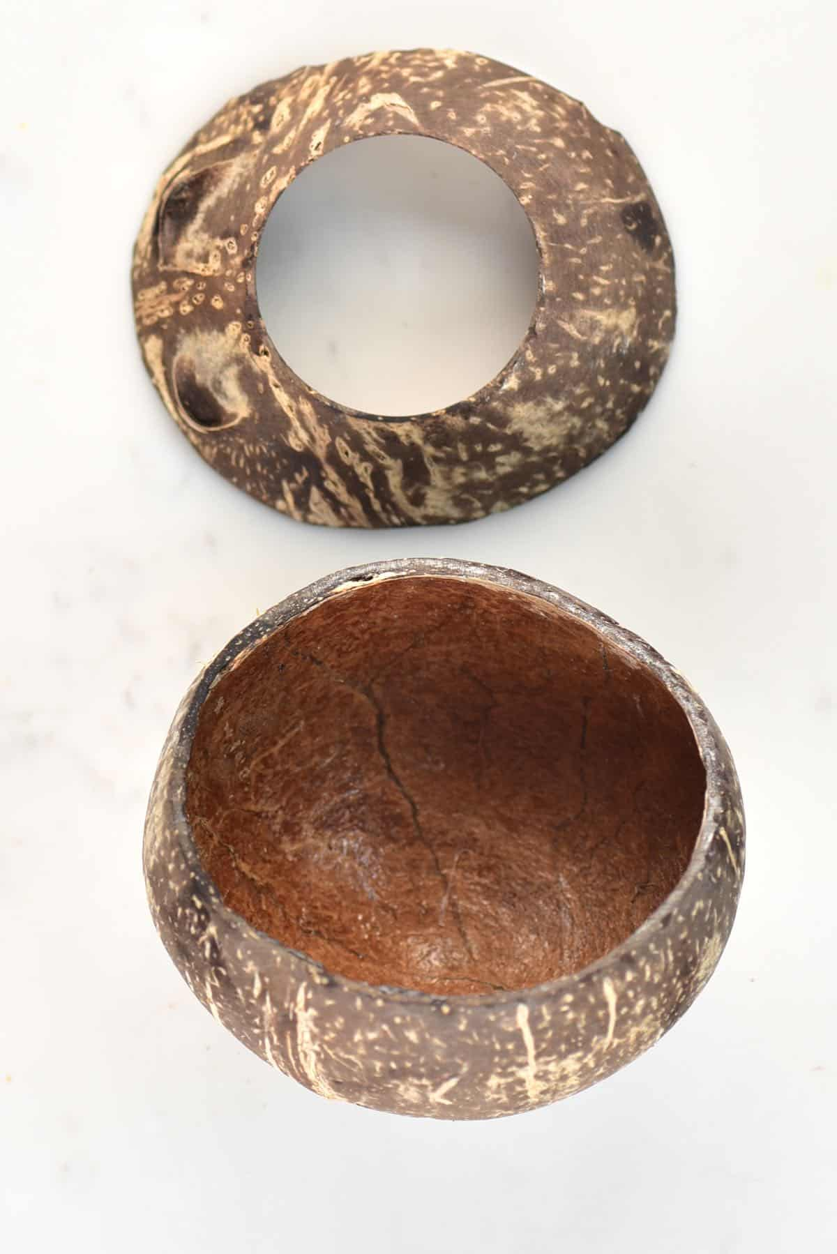 A coconut shell bowl on a flat white surface