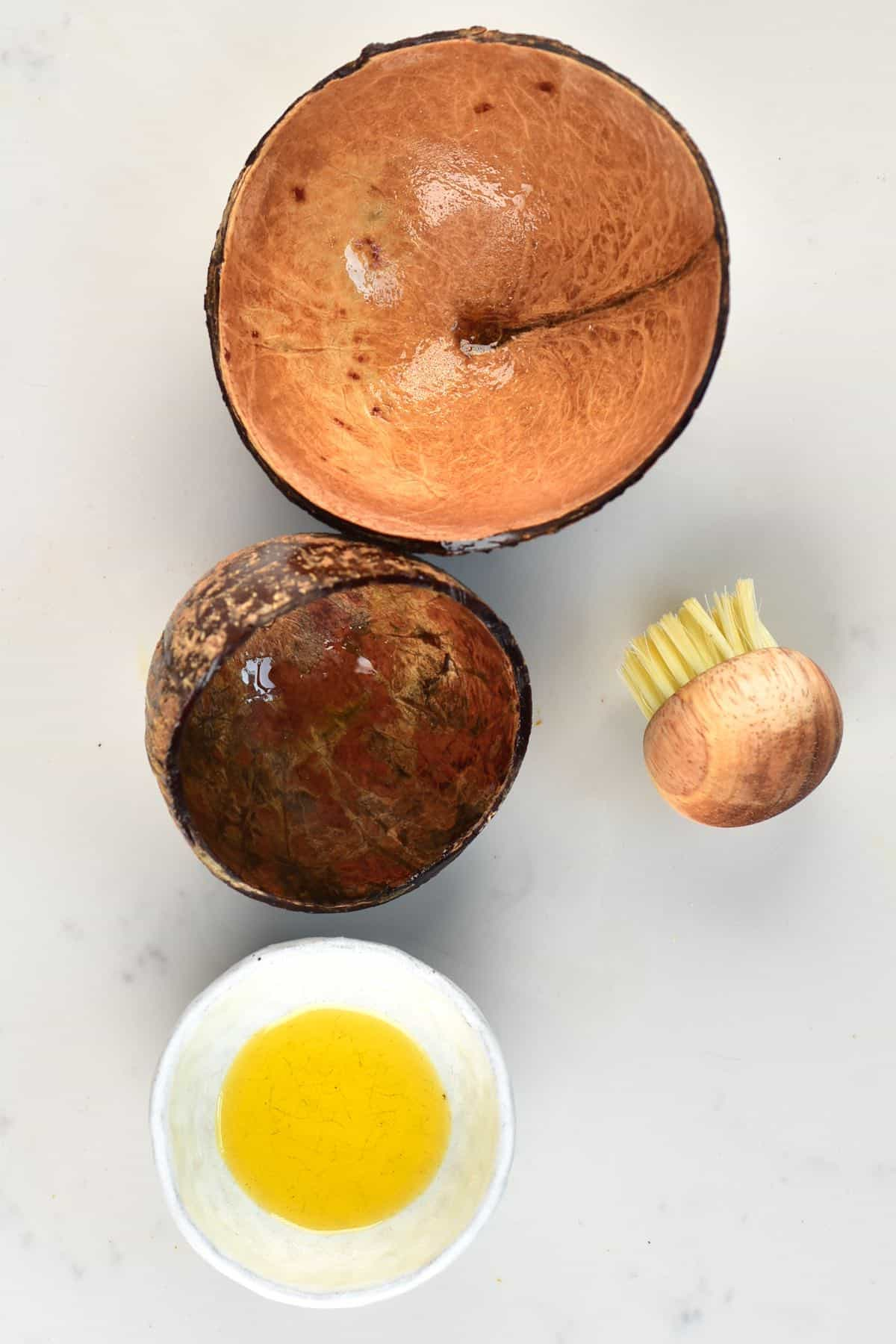 Two coconut shell bowls and a little bowl with oil with a brush