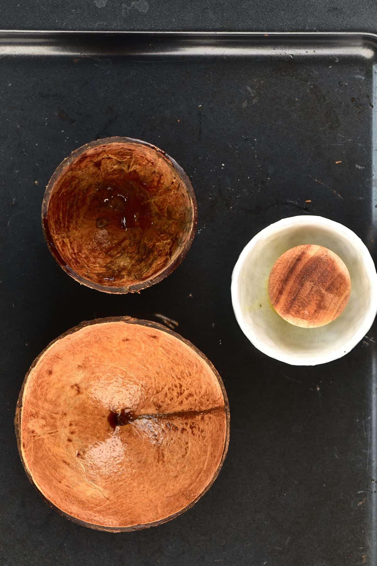 Two coconut shell bowls on a baking tray with a little bowl with oil and brush