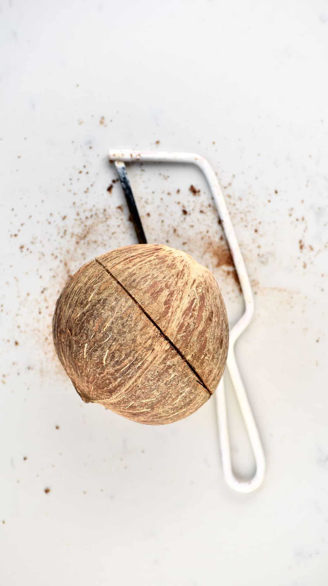 A coconut cut through the middle and a saw next to it on a flat white surface
