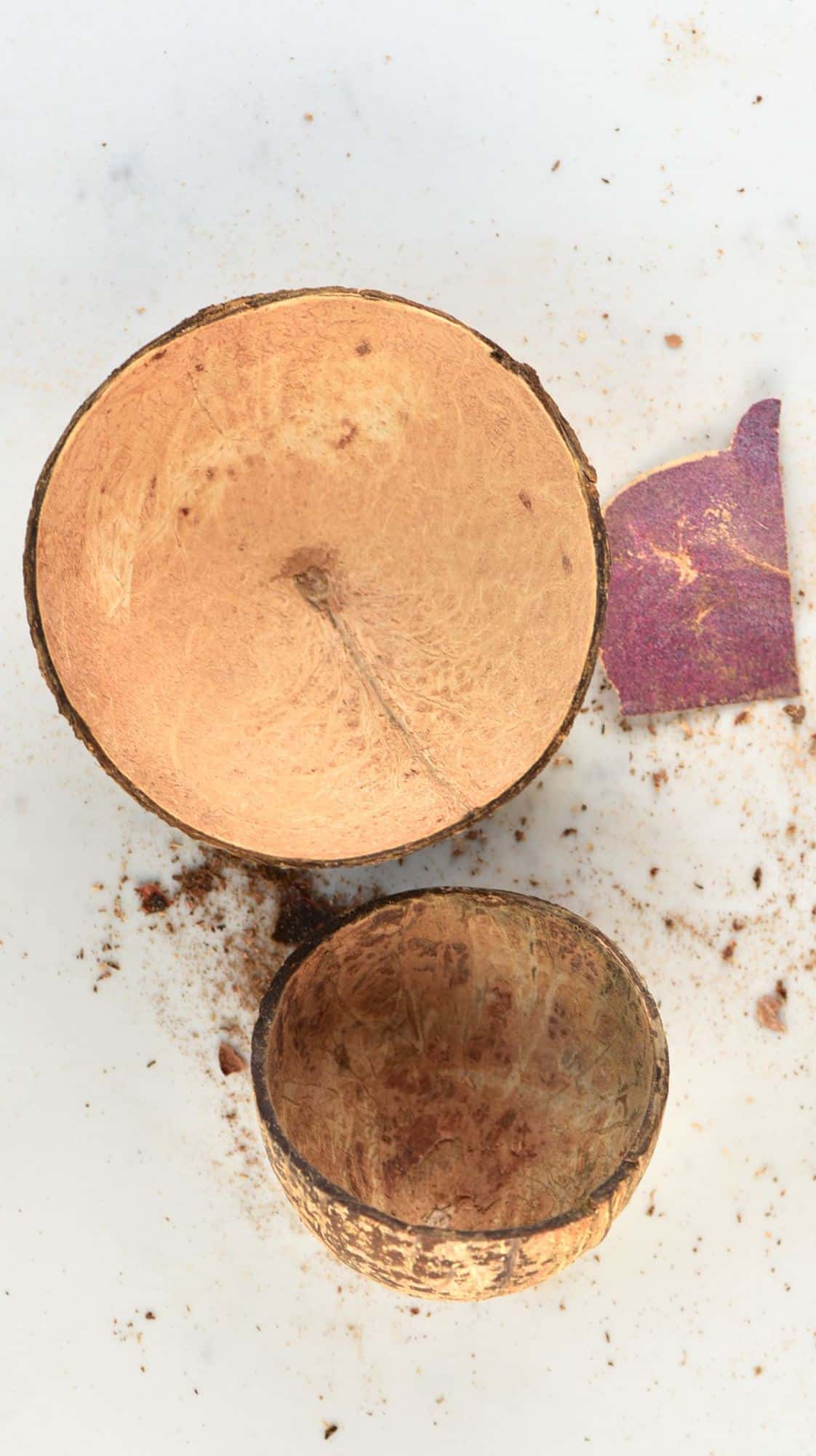Two coconut bowls and a piece of sandpaper
