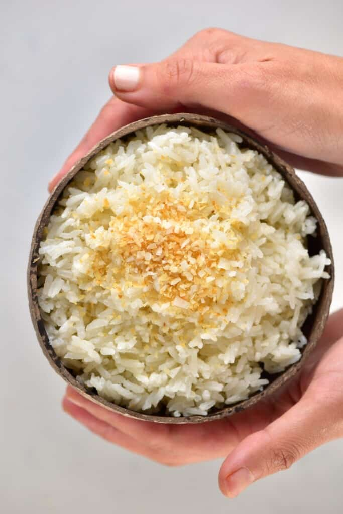 Two hands holding a coconut bowl with coconut rice