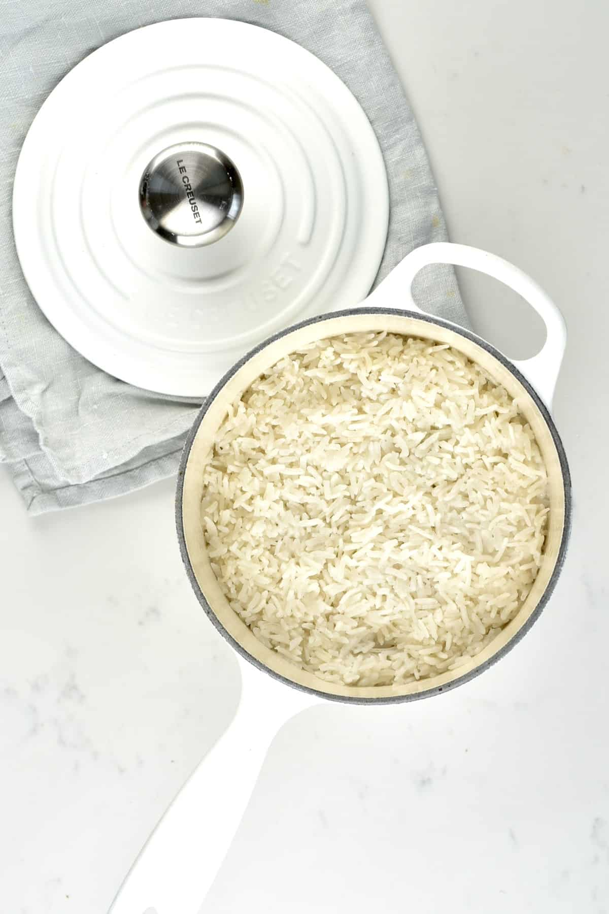 A pot with coconut rice and its cover on the side