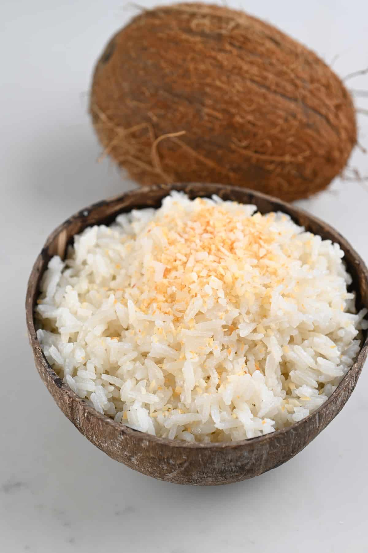 A coconut bowl filled with coconut rice and a whole coconut behind it