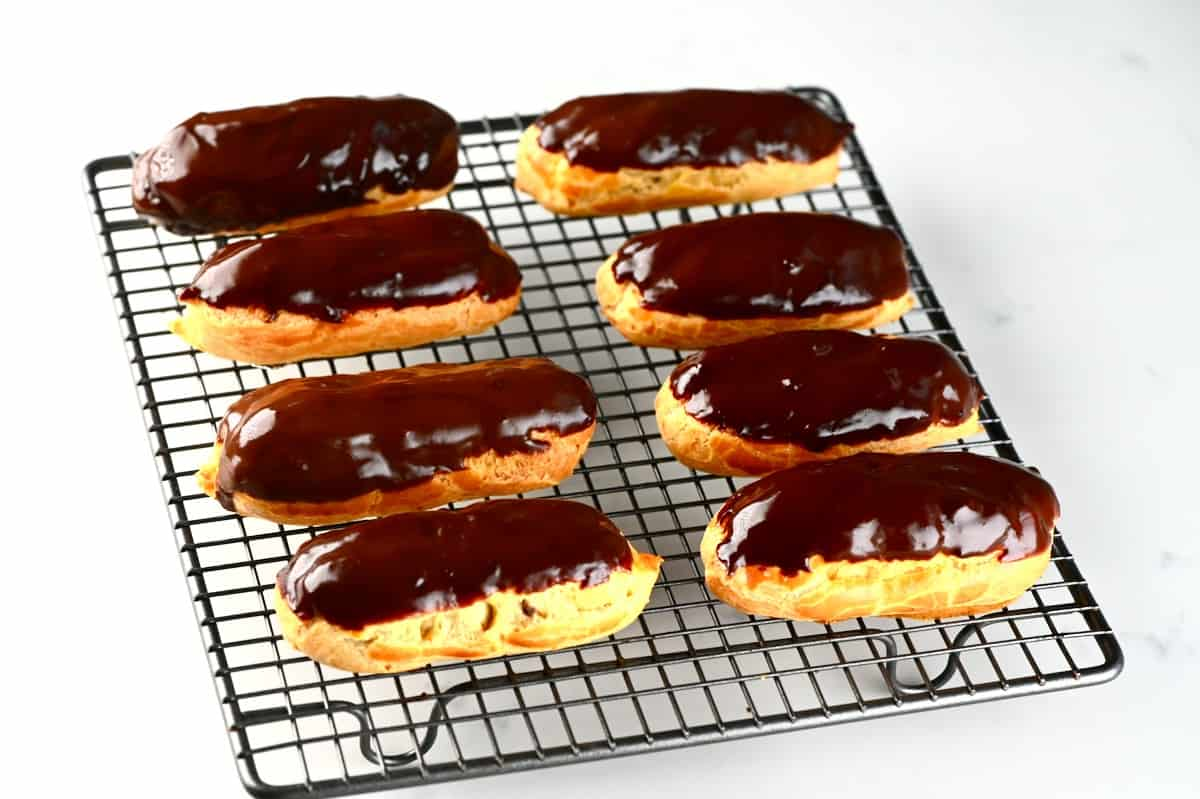 Eight chocolate glazed eclairs on a cooling rack