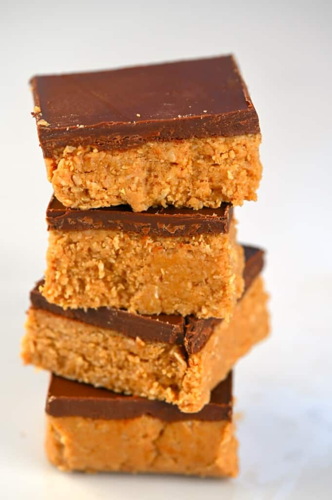 Four peanut butter bars with chocolate coating stacked on top of each other