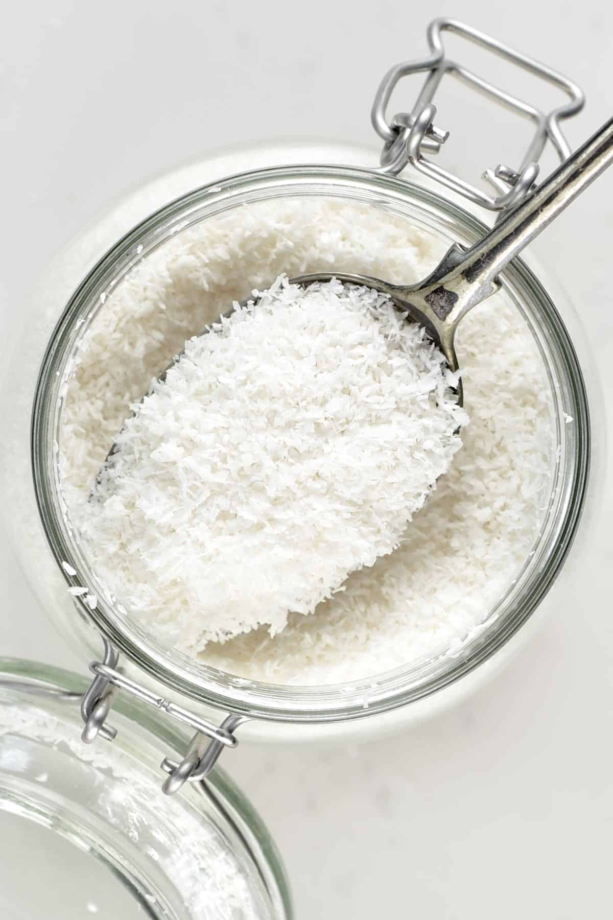 A spoonful of Shredded Coconut over a jar