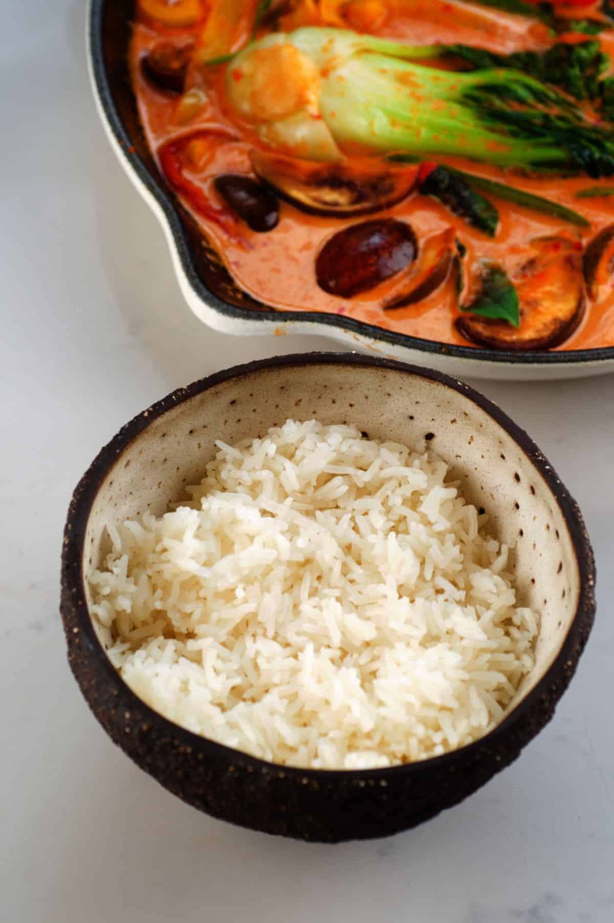 Jasmine rice in a bowl and Thai Red Curry in a pan