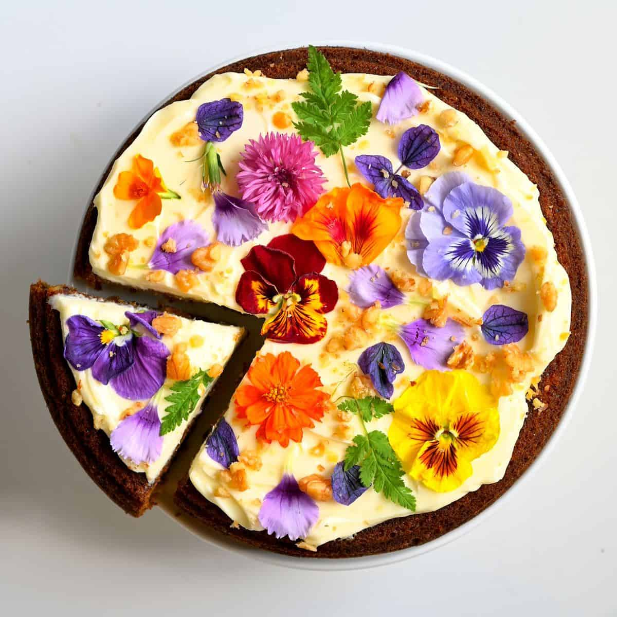 Carrot Cake with frosting and edible flowers and a cut slice