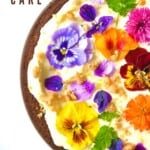 A top view of carrot cake with cream cheese frosting and edible flowers
