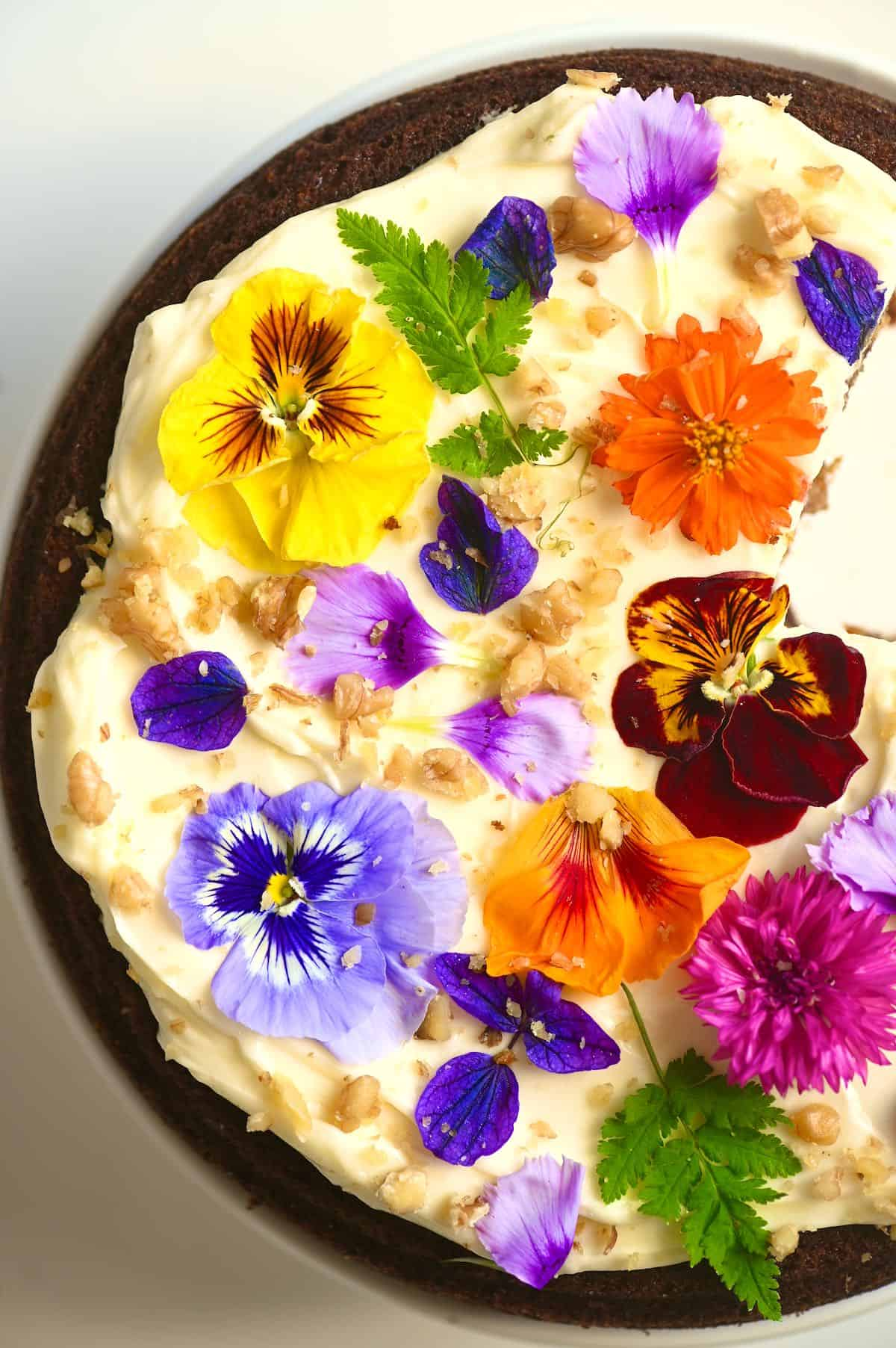 A close up of carrot cake with cream cheese frosting and edible flowers