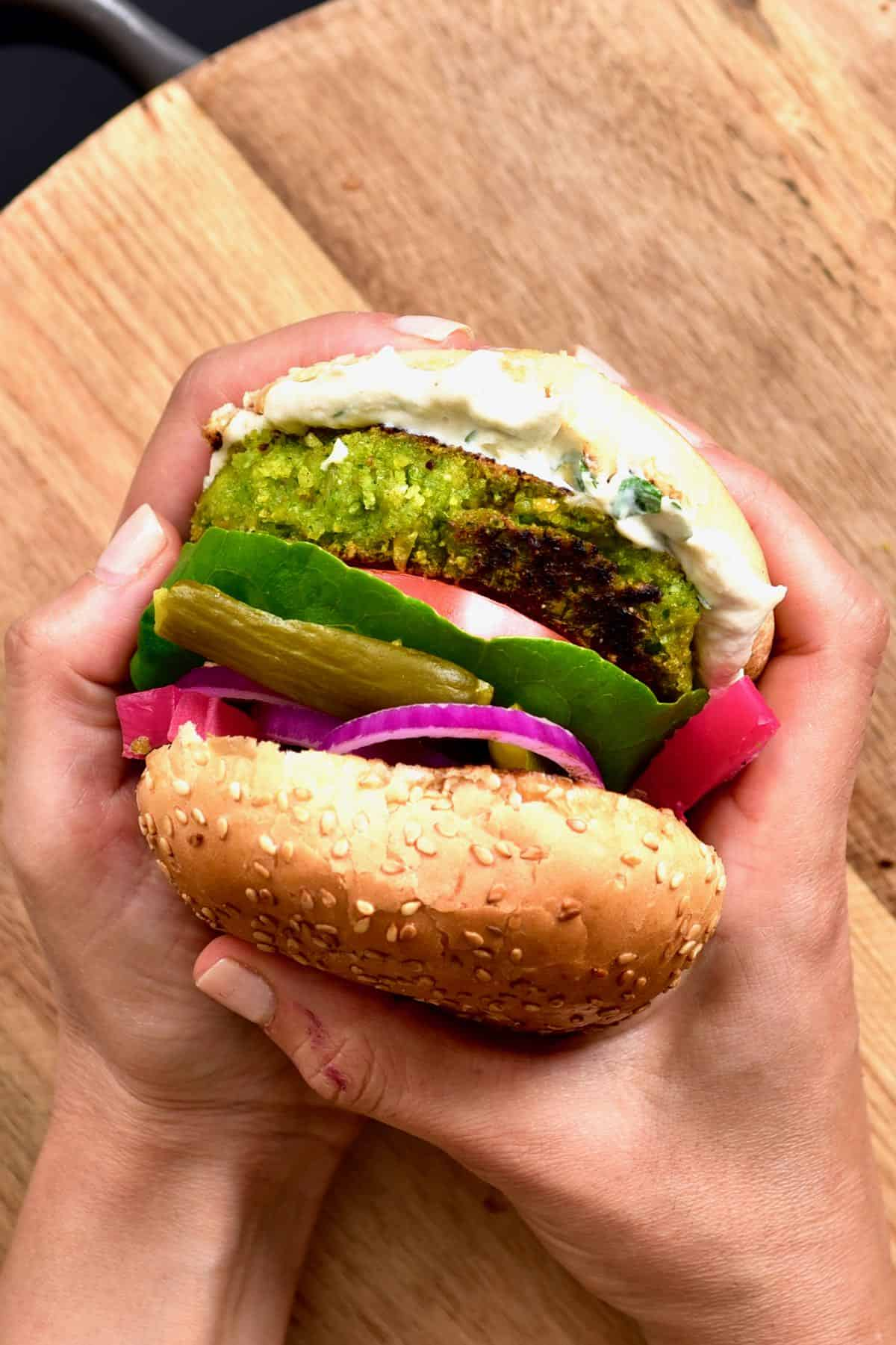 Hands holding a burger with onion, pickles, lettuce, tomato and falafel patty