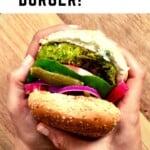 Hands holding a falafel burger