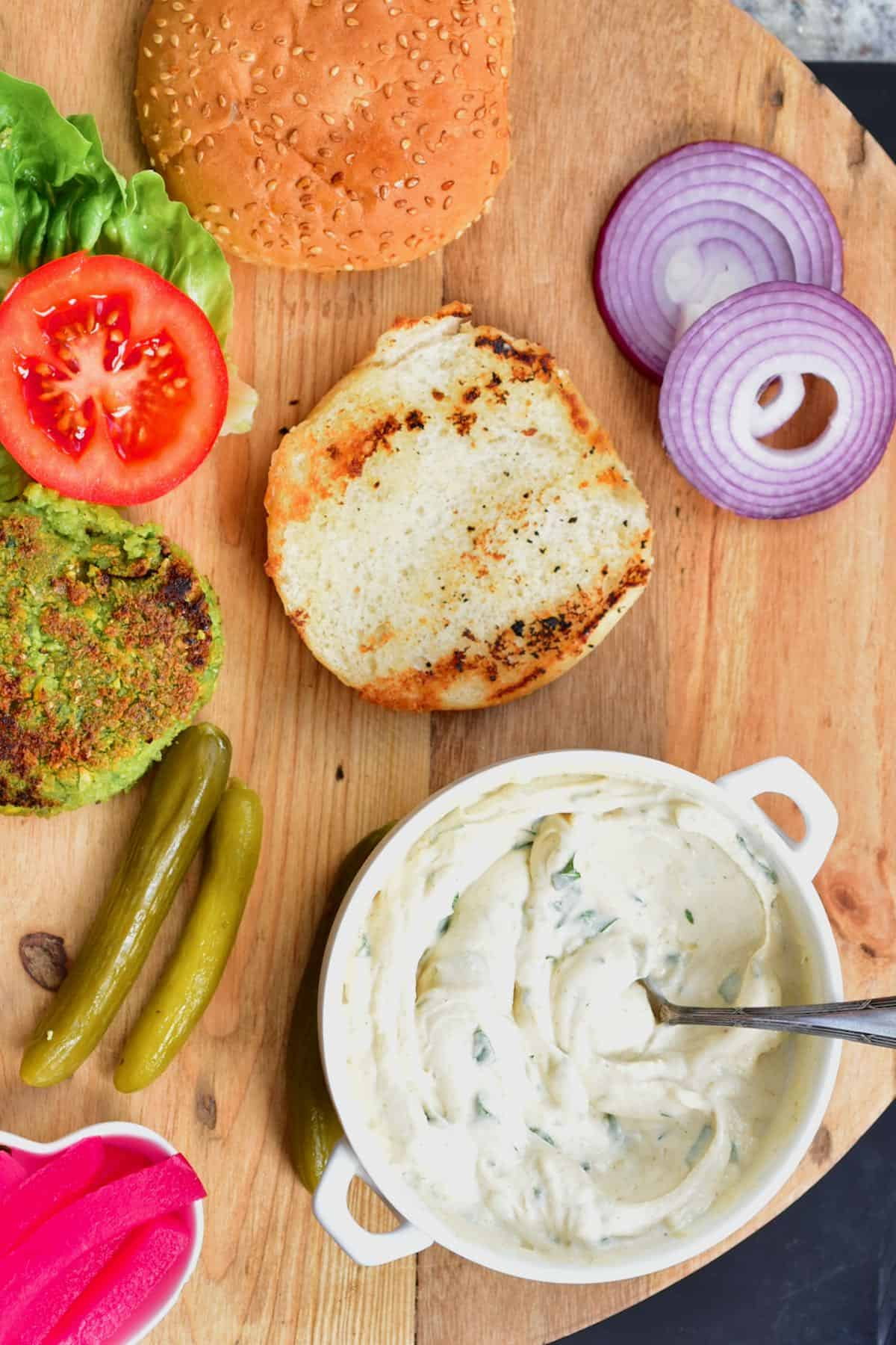 Tahini sauce in a bowl and burger ingredients on a chopping board