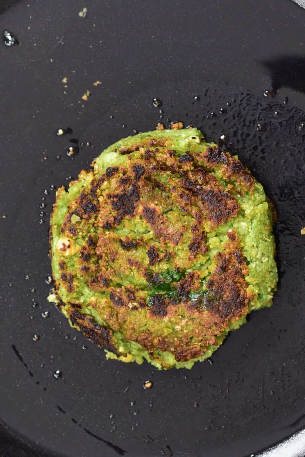 A falafel patty laying on a dark flat surface