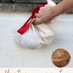 A coconut in a tote bag being hit against a wall as a way to open it
