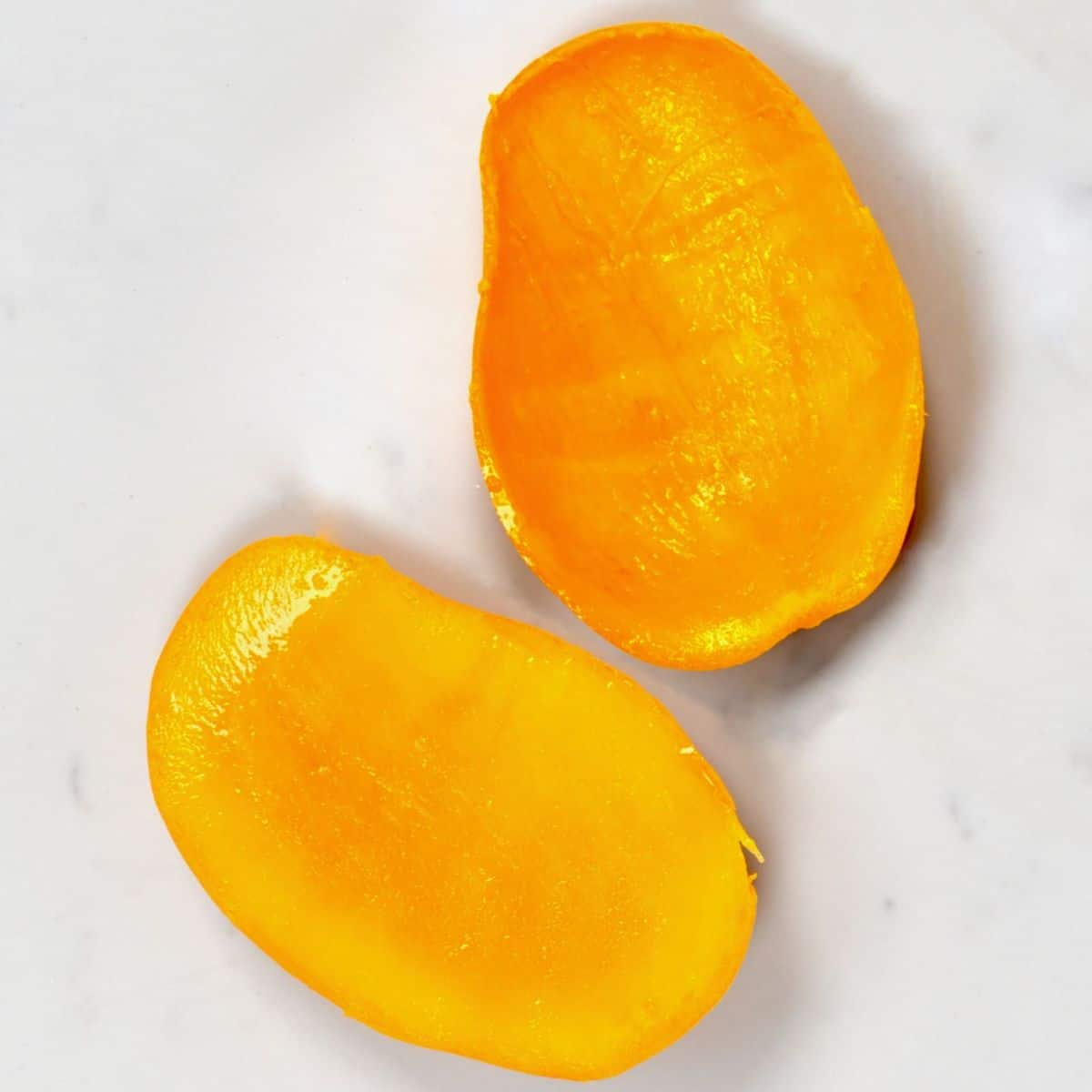 Two mango halves on a flat surface